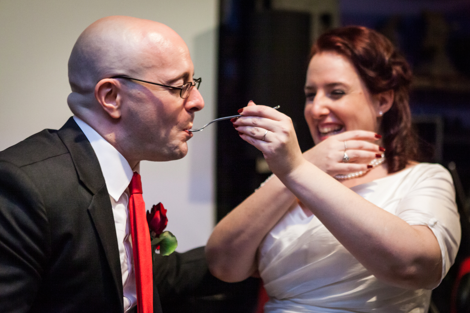 Bride feeding cake to groom at a DUMBO wedding