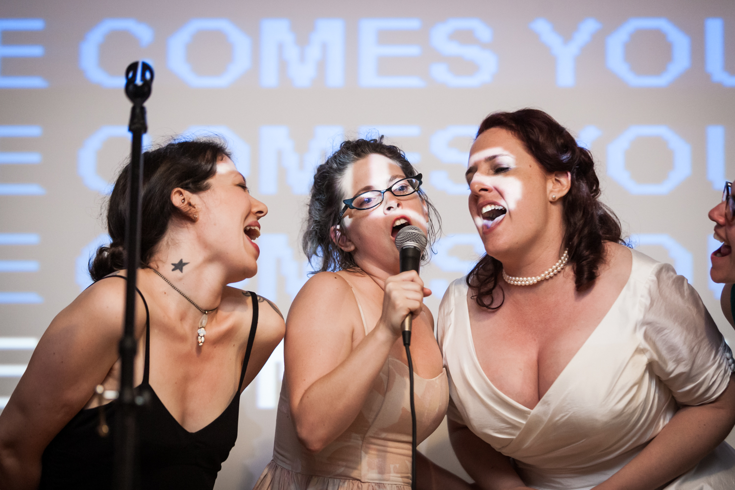 Bride singing karaoke with two female guests at a DUMBO wedding