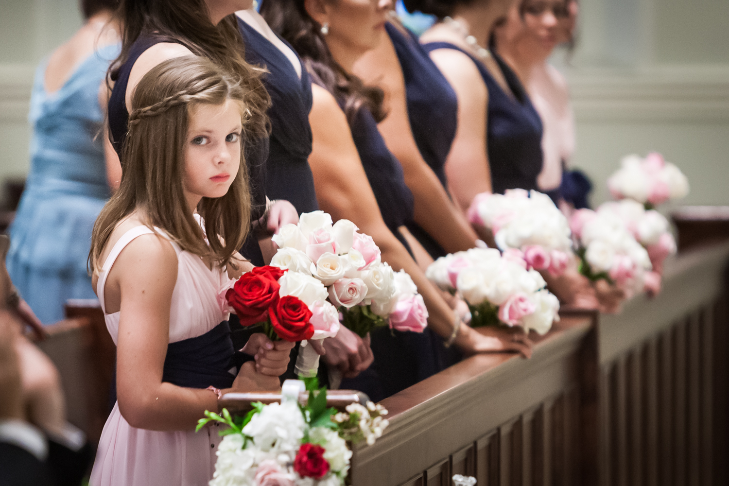 Young flower girl holding bouquet with bridesmaids in background