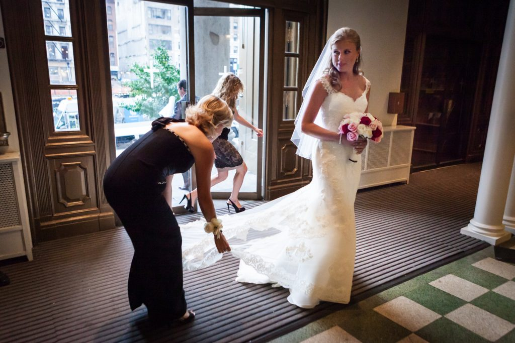 Bridesmaids fixing bride's train before she enters St. Peter's Church