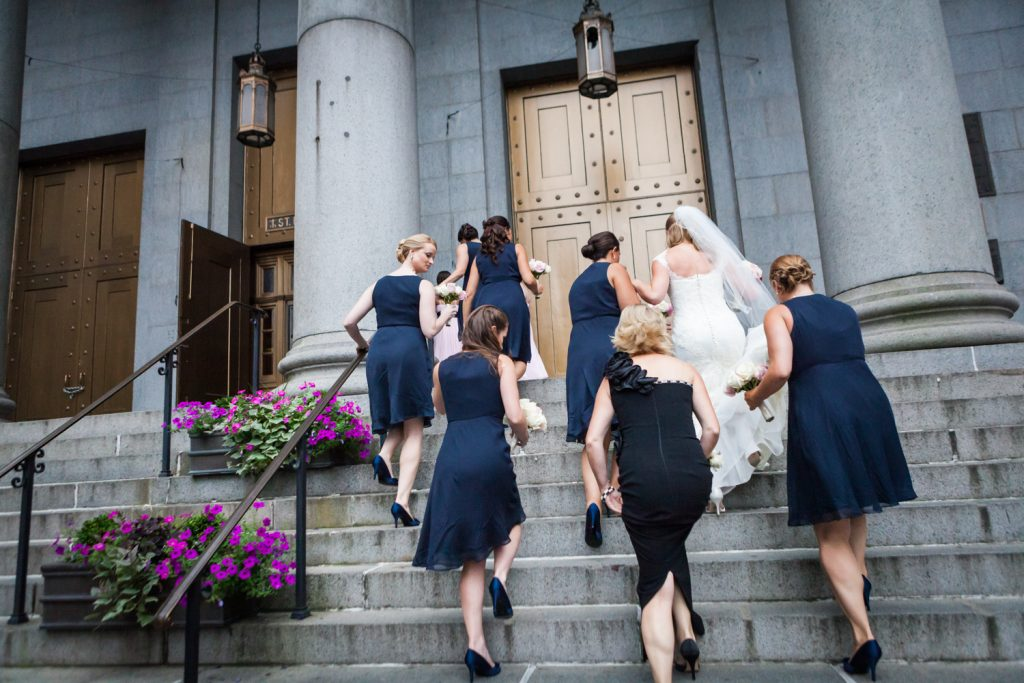 Bride and bridesmaids walking up the steps of St. Peter's Church for a wedding ceremony