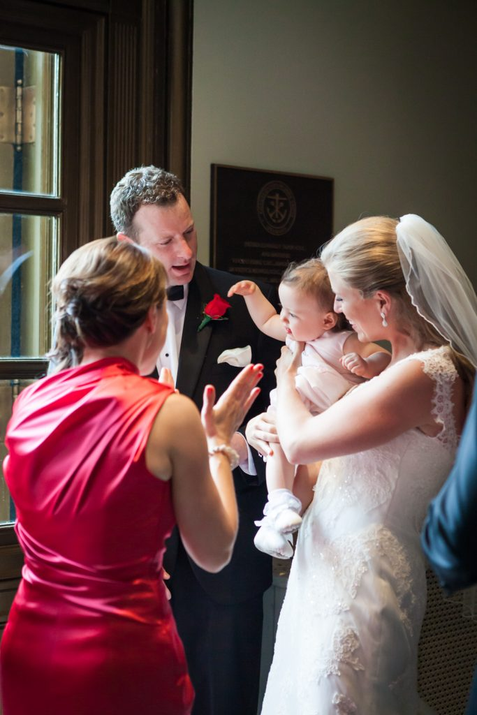 Bride and groom playing with baby after St. Peter's Church wedding ceremony