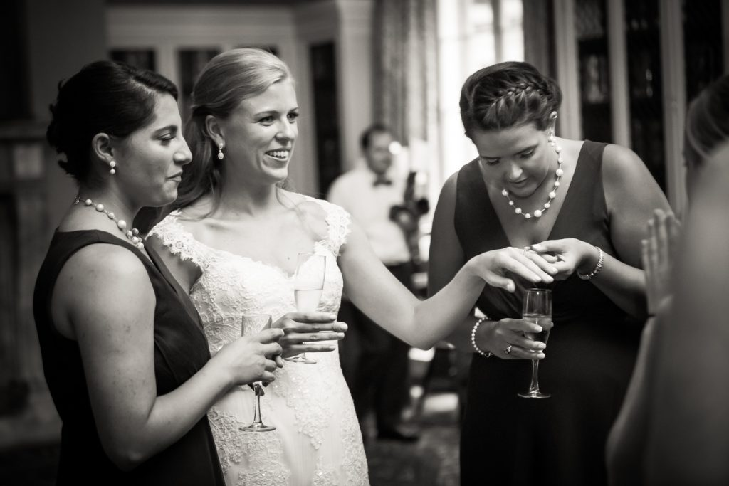 Black and white photo of bride showing off wedding ring to girlfriends