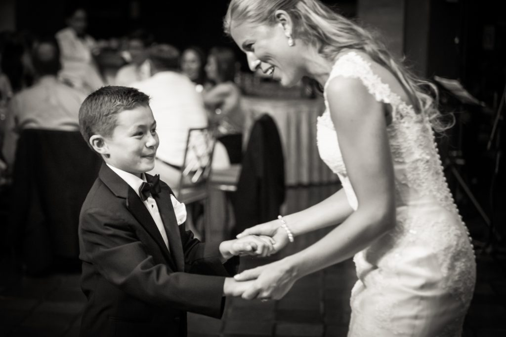 Black and white photo of bride dancing with young boy