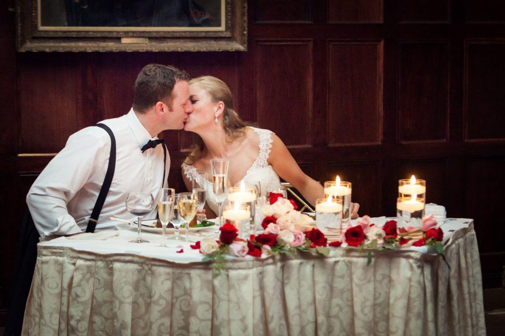 Bride and groom kissing at sweetheart table at a Harvard Club NYC wedding