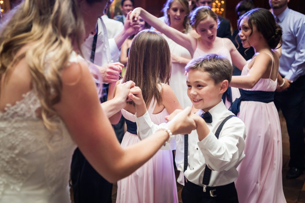 Bride dancing with young boy wearing bow tie