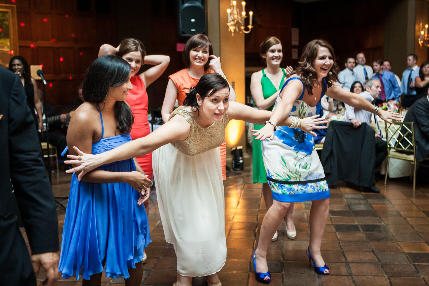 Woman holding back other female guests during bouquet toss