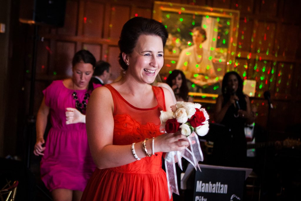 Female guest holding bouquet and wearing red dress