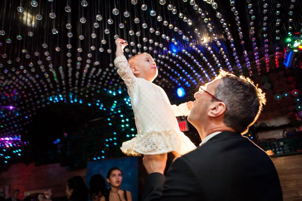 Baby reaching up for glittery ceiling at a bar mitzvah