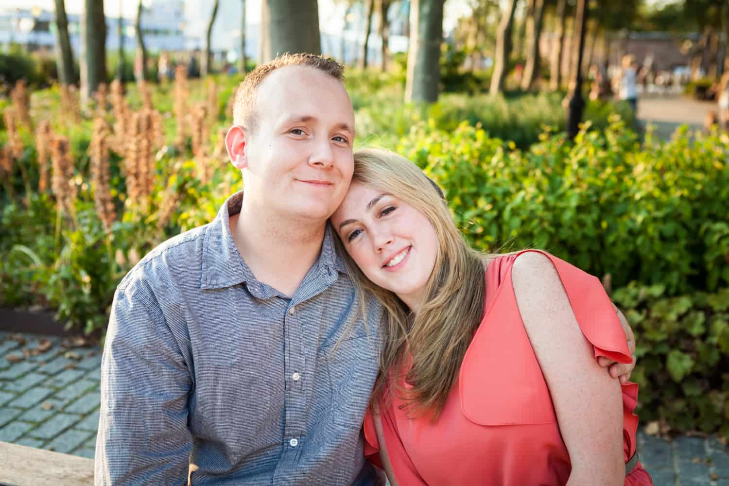 Couple sitting on bench at a Battery Park engagement shoot
