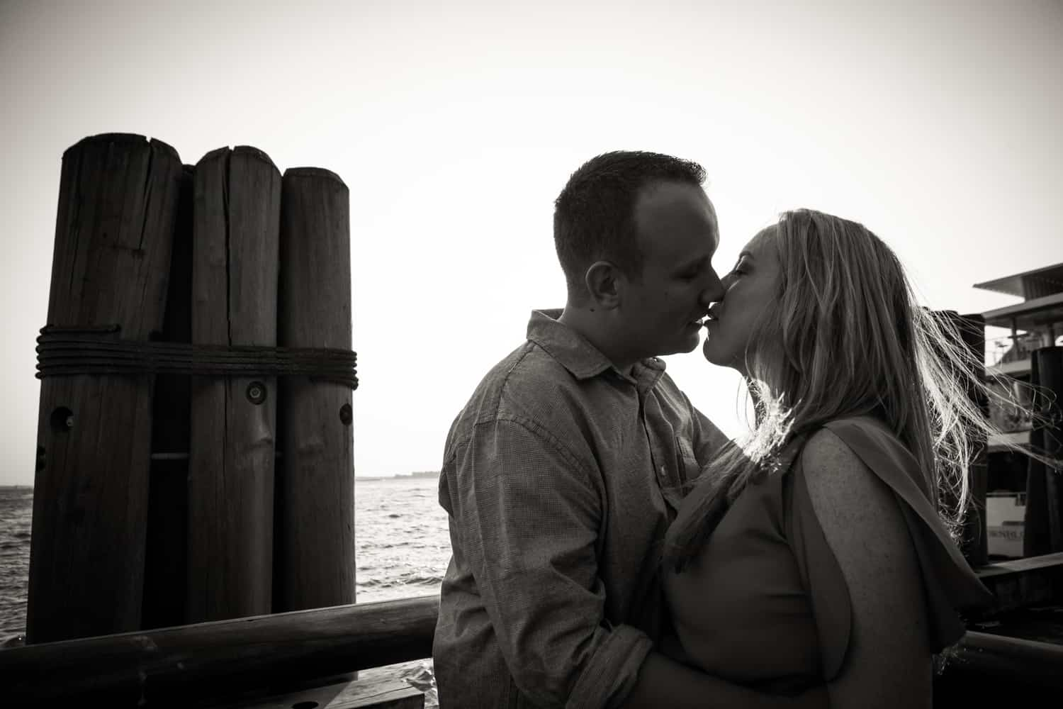 Black and white photo of couple kissing in Battery Park