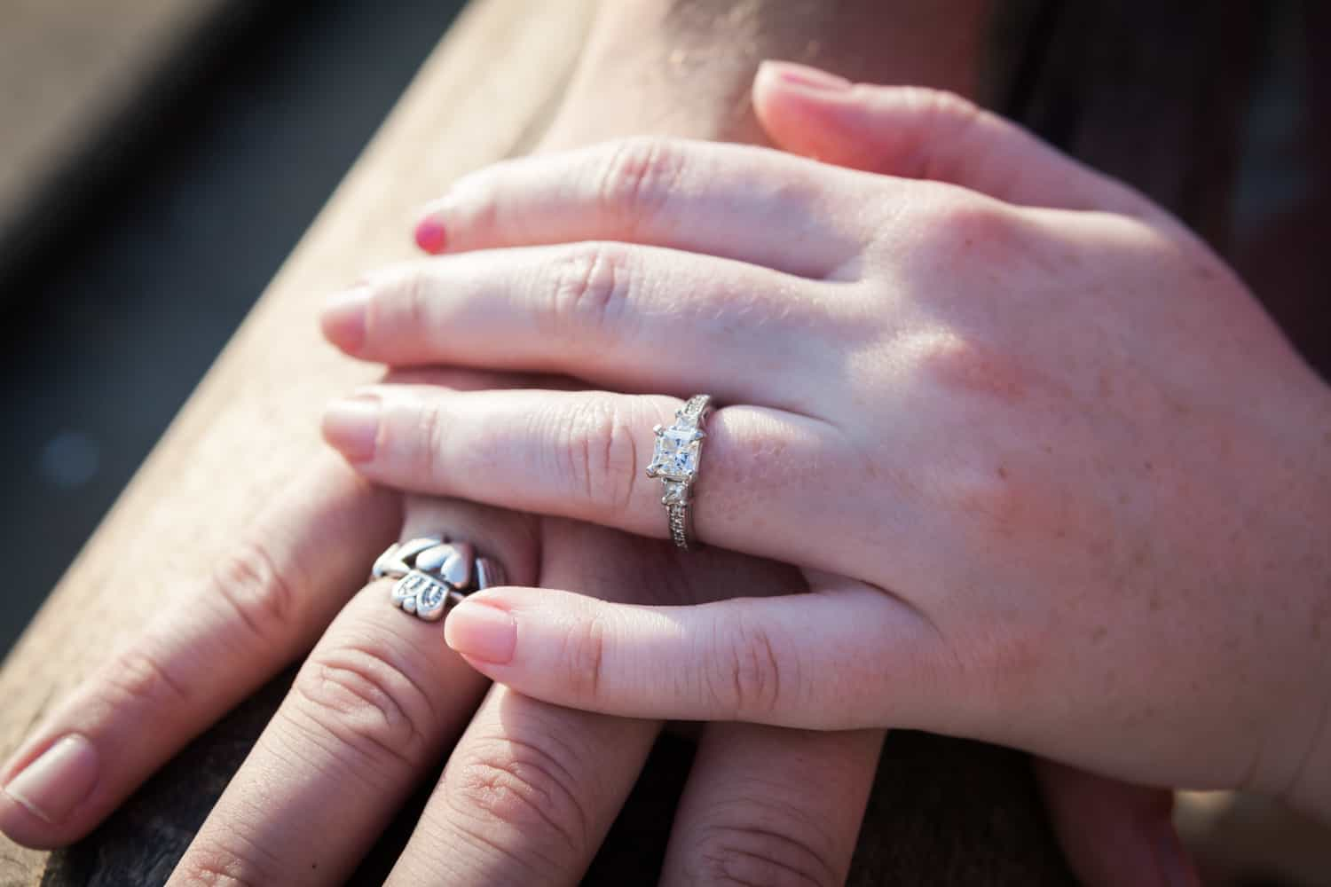 Close up on hands of couple wearing engagement rings