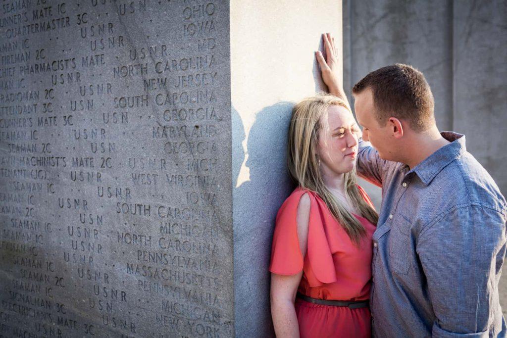 Couple leaning against concrete monument at a Battery Park engagement shoot