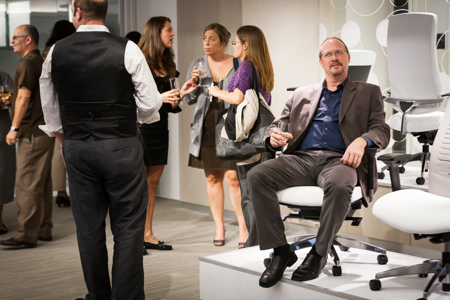 Guest seated in chair on display during corporate cocktail party