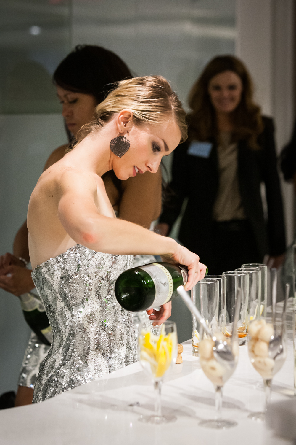 Woman wearing silver dress pouring champagne into glasses