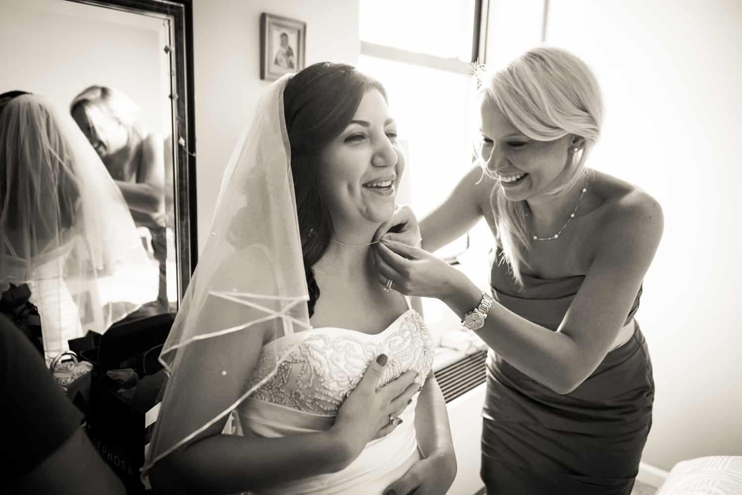 Black and white photo of bridesmaid adjusting bride's necklace