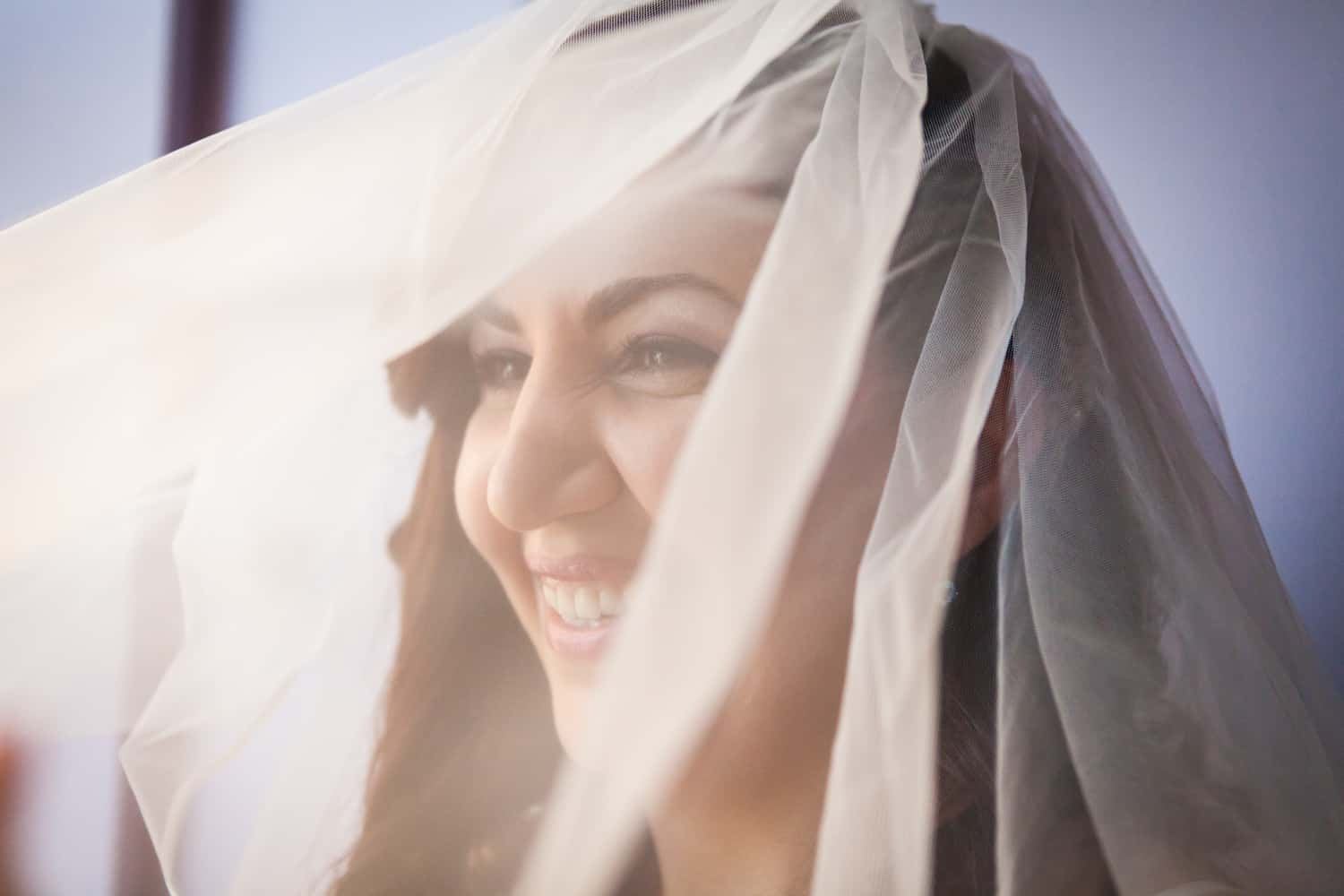 Bride laughing under veil