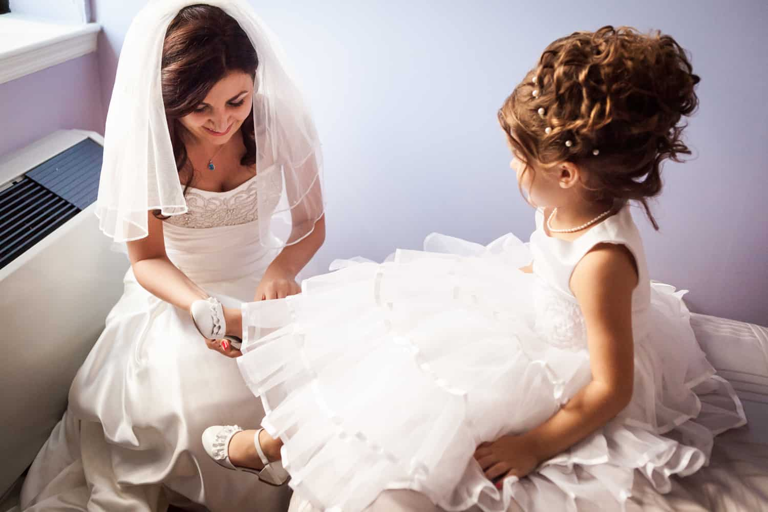 Bride helping flower girl put on her shoe