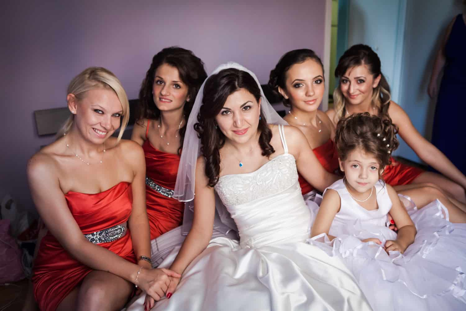 Bride and bridesmaids sitting on bed