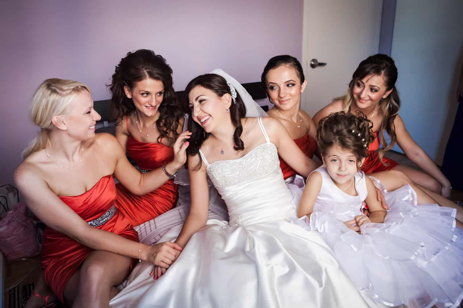 Bride and bridesmaids laughing on bed