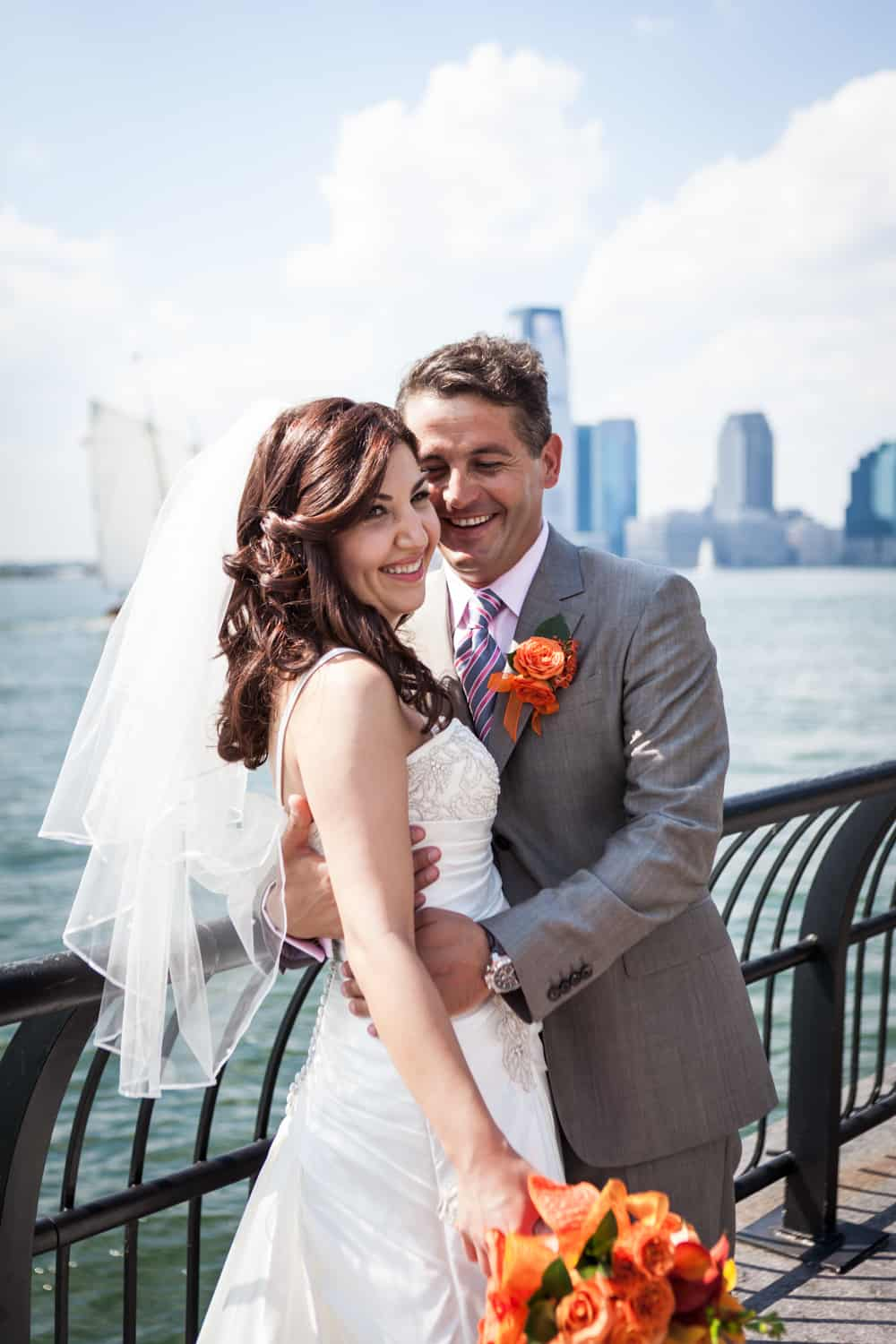 Bride and groom hugging by railing of NYC waterfront