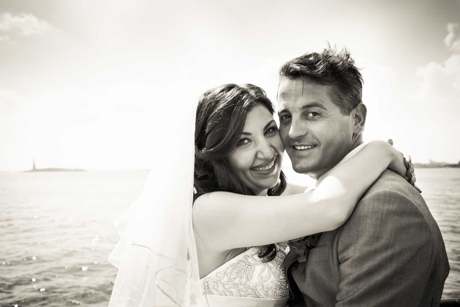 Black and white photo of bride and groom by waterfront