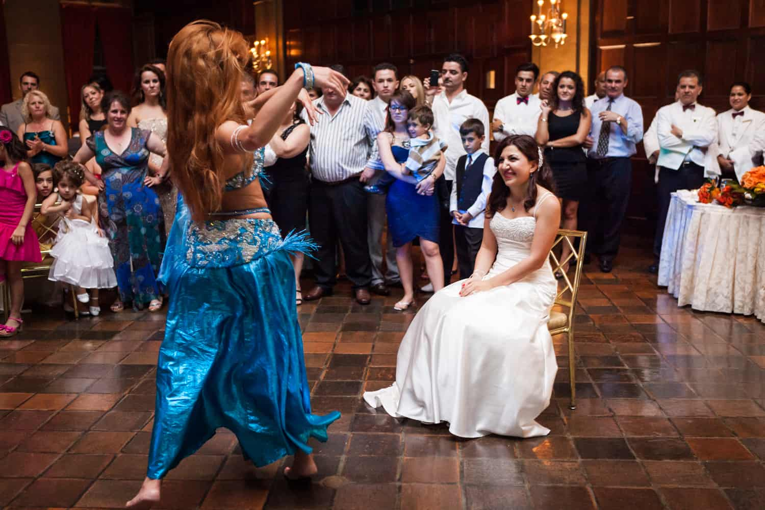 Bride sitting in front of belly dancer at a Harvard Club wedding