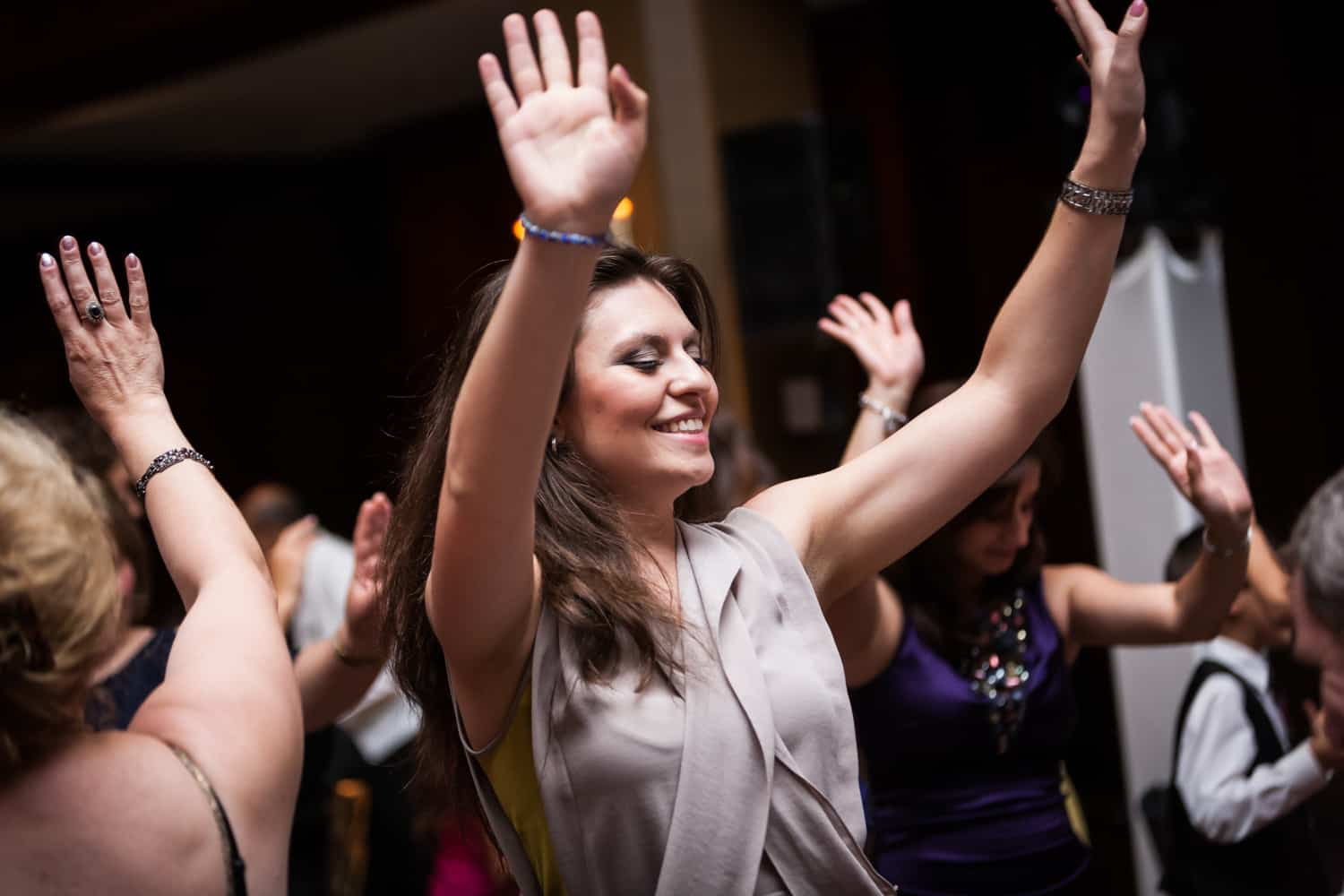 Female guest dancing with hands raised at a Harvard Club wedding