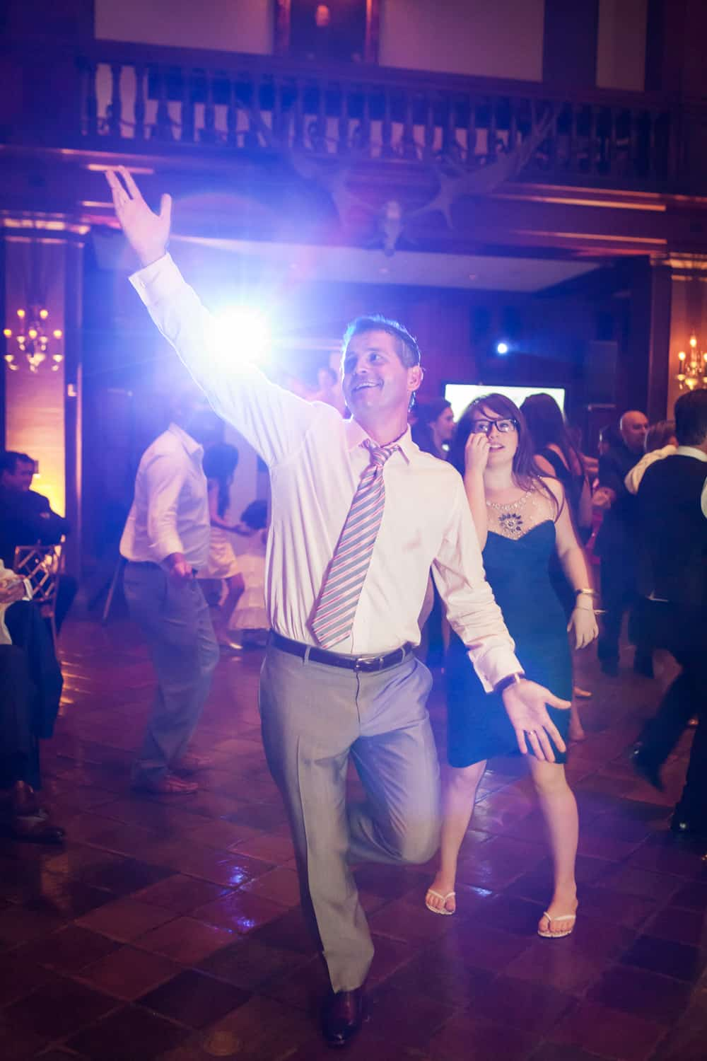 Groom dancing with hands raised at a Harvard Club wedding