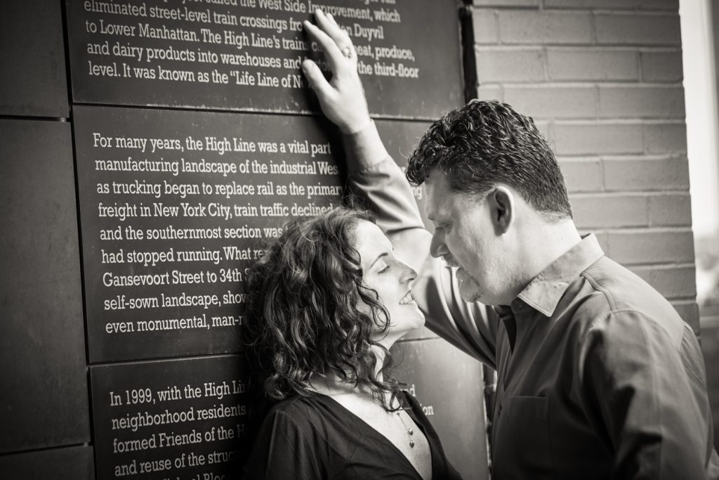 Black and white photo of couple leaning against High Line plaque