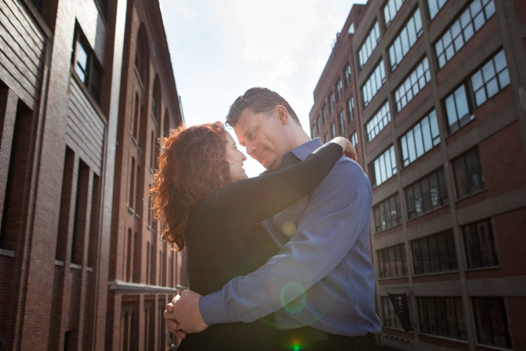 High Line engagement photos of couple looking at each other with factory in background