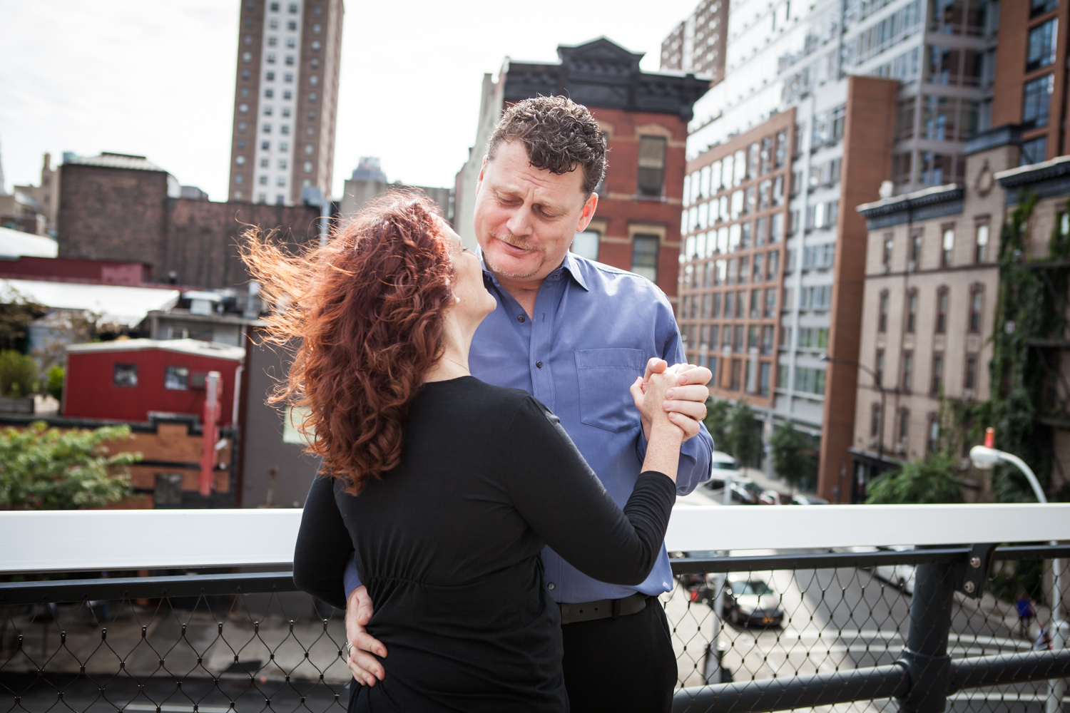 Couple dancing together on the High Line observation deck with NYC street in background