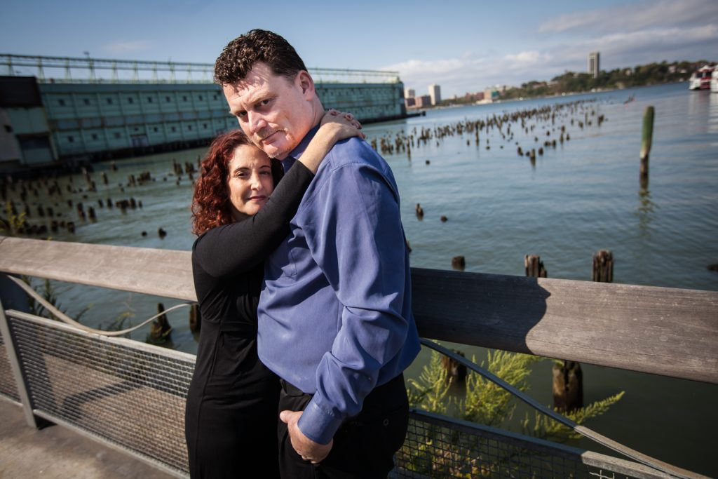 Couple standing in front of Hudson River waterfront