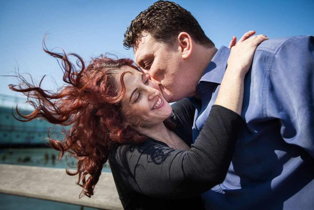 Man kissing woman with her hair flying