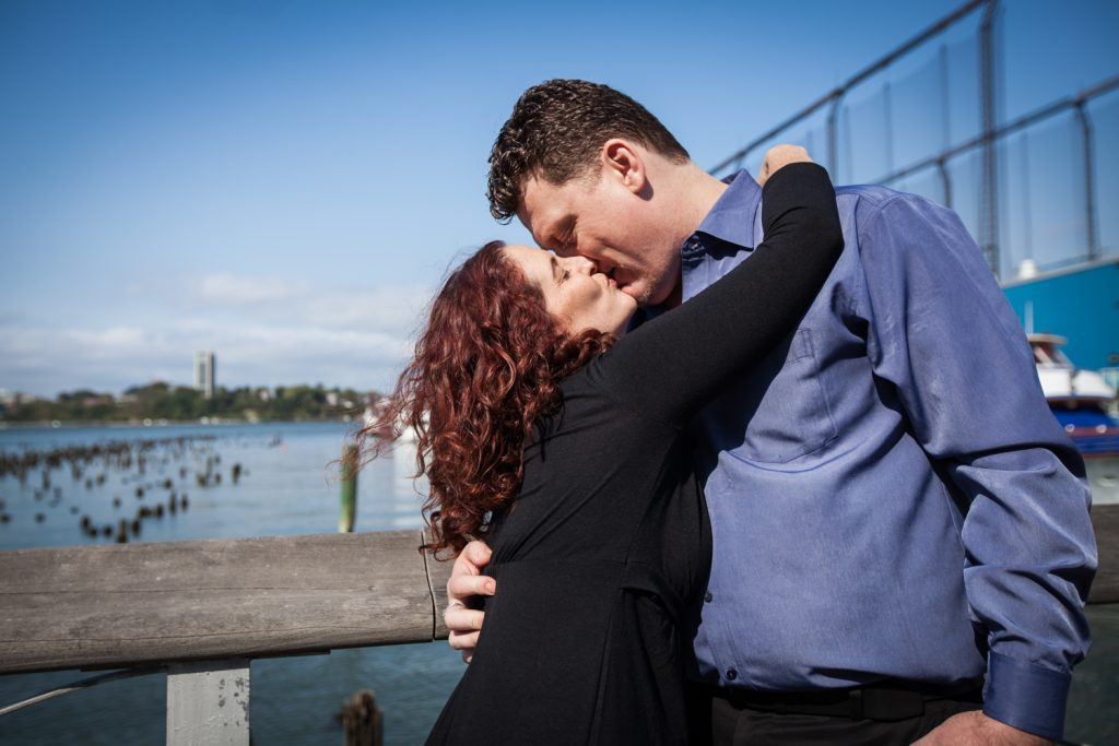 Couple kissing in front of Hudson River waterfront