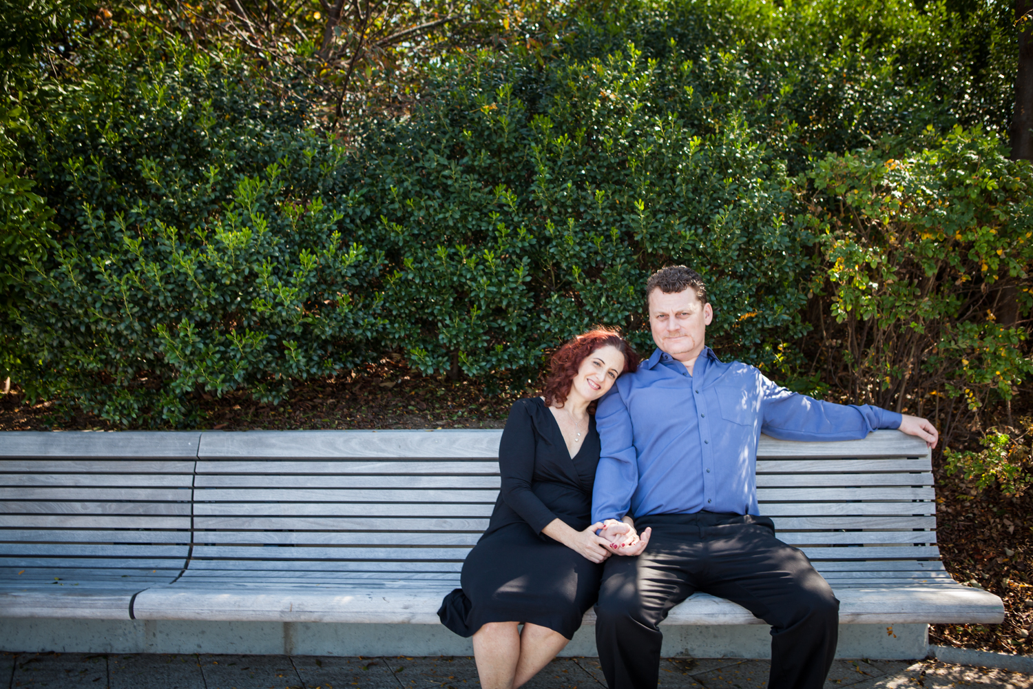 Couple sitting together on bench in park