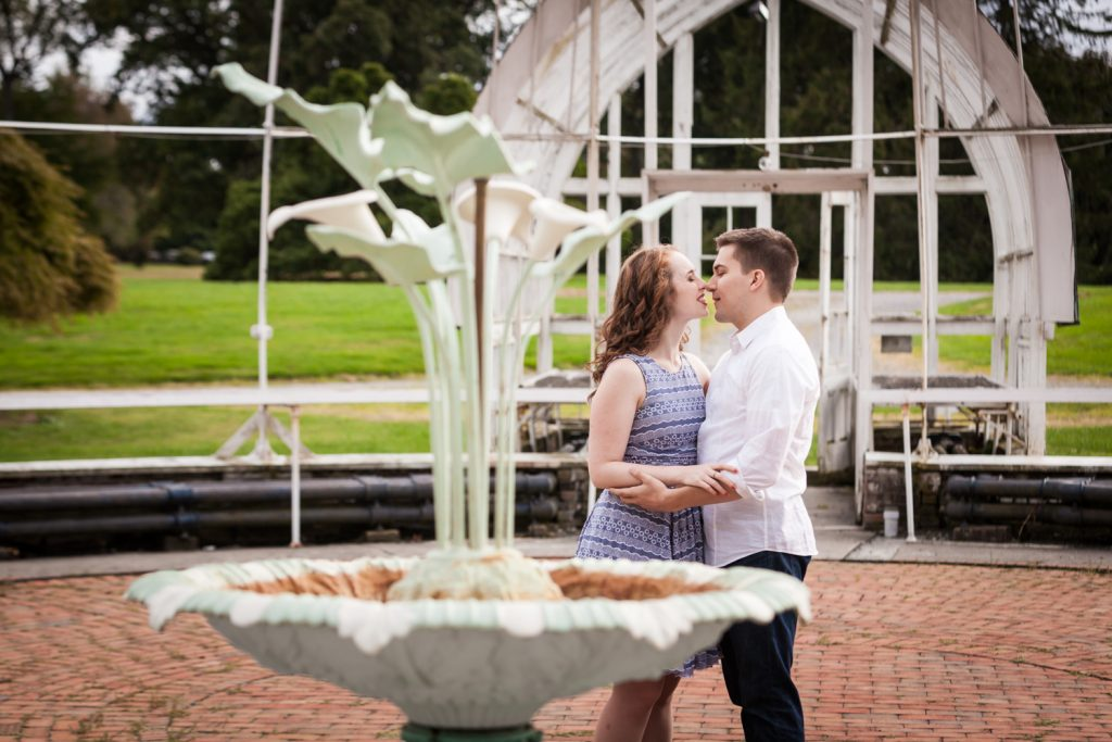 Couple kissing behind elaborate fountain at a Lyndhurst Mansion engagement photoshoot