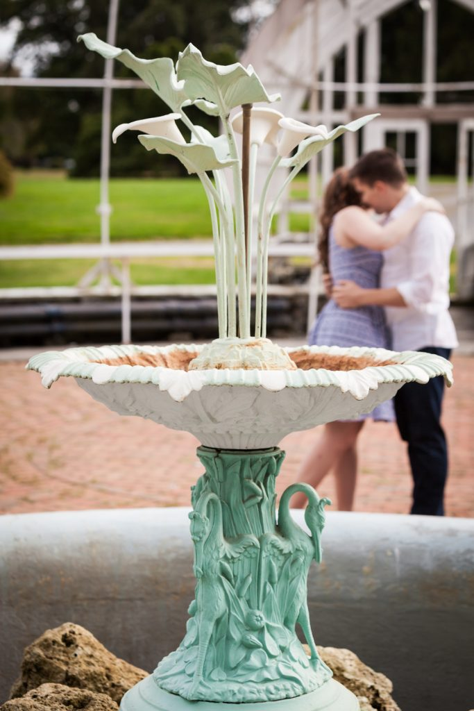 Elaborate fountain in greenhouse with couple kissing in background at a Lyndhurst Mansion engagement photoshoot