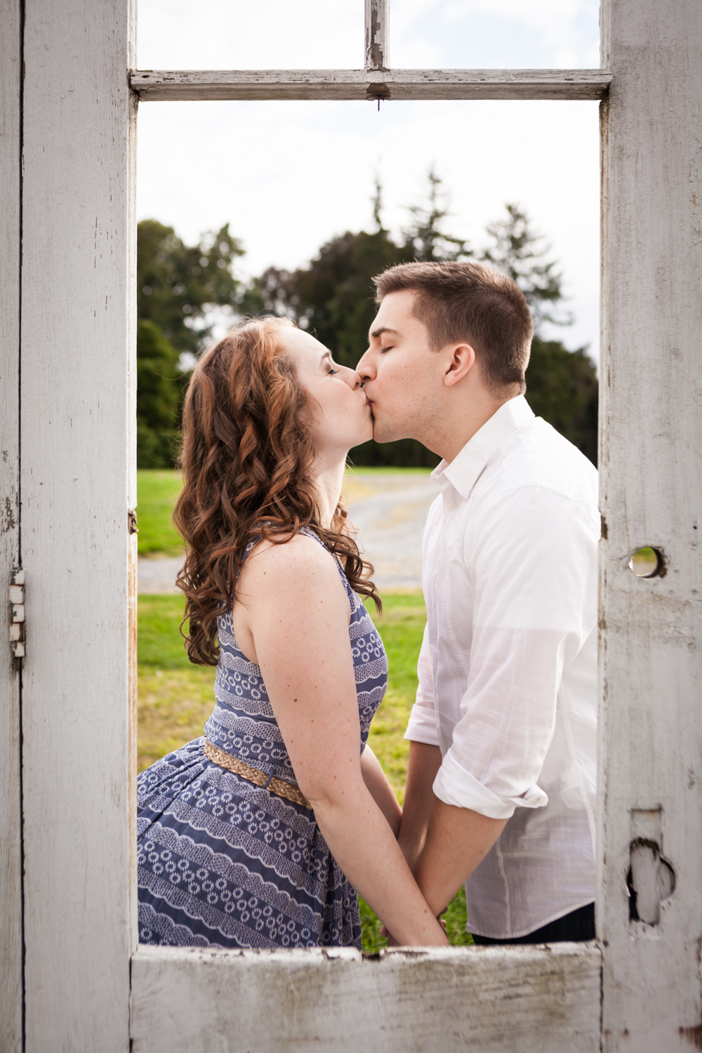 View of couple kissing through door at a Lyndhurst Mansion engagement photoshoot