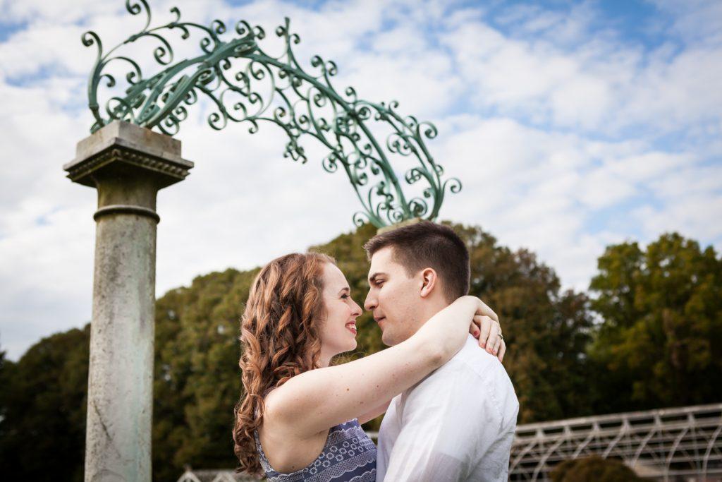 Couple underneath elaborate gate at a Lyndhurst Mansion engagement photoshoot