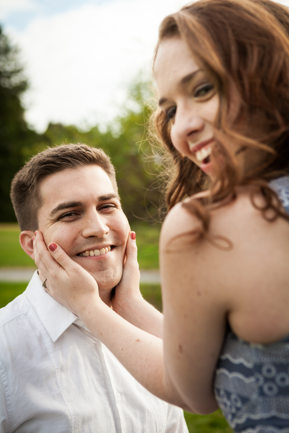 Woman holding man's face at a Lyndhurst Mansion engagement photoshoot
