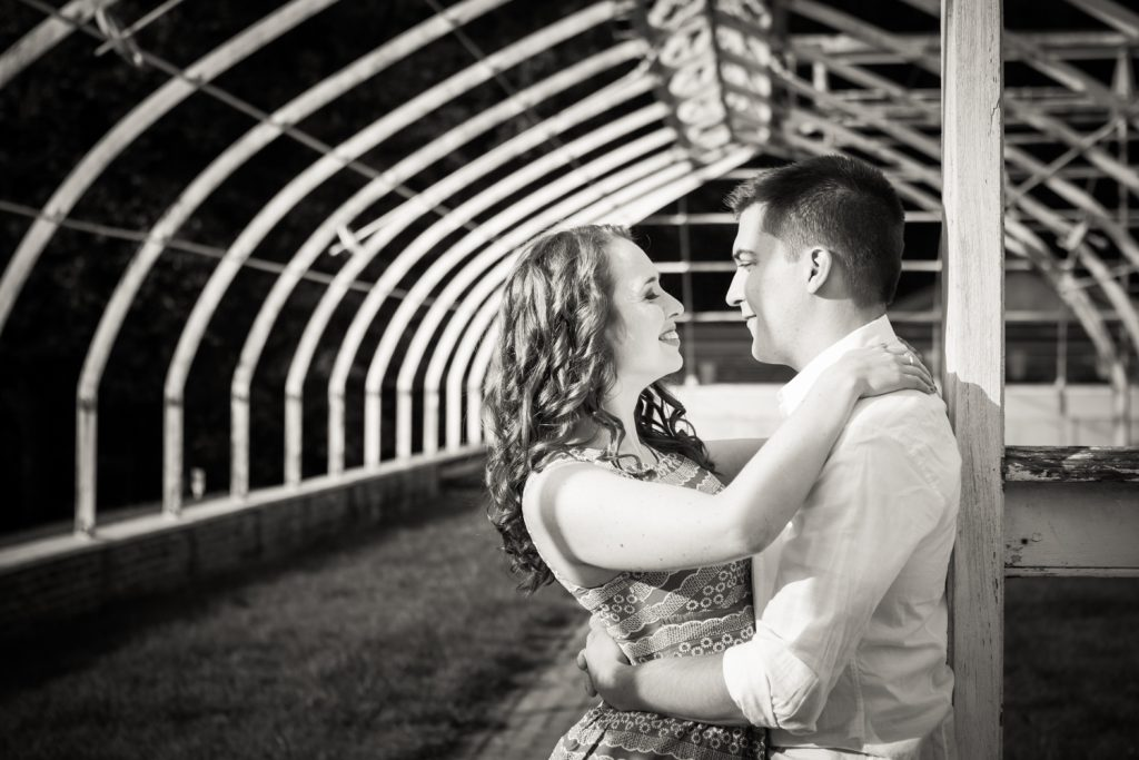 Black and white photo of couple in dilapidated greenhouse