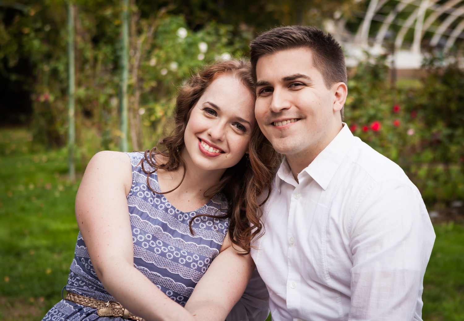 Couple in front of rose bushes at a Lyndhurst Mansion engagement photoshoot