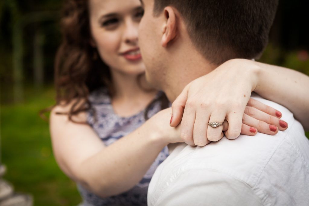 Close up on woman's hand wearing engagement ring as she hugs man