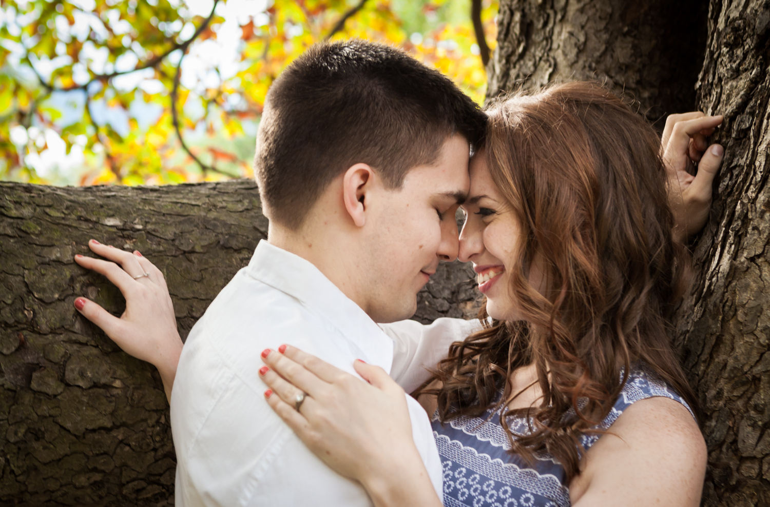 Couple touching foreheads next to tree