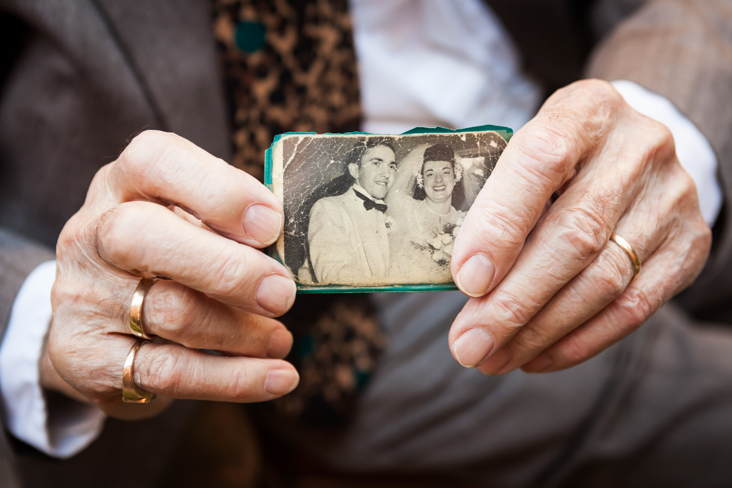 Close up on grandfather's hands holding black and white wedding portrait