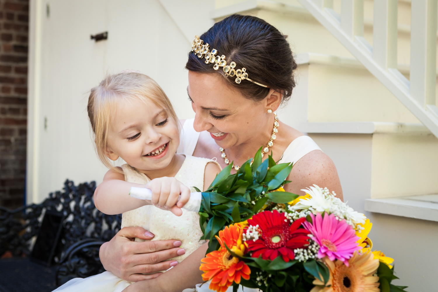 Bride playing with little flower girl