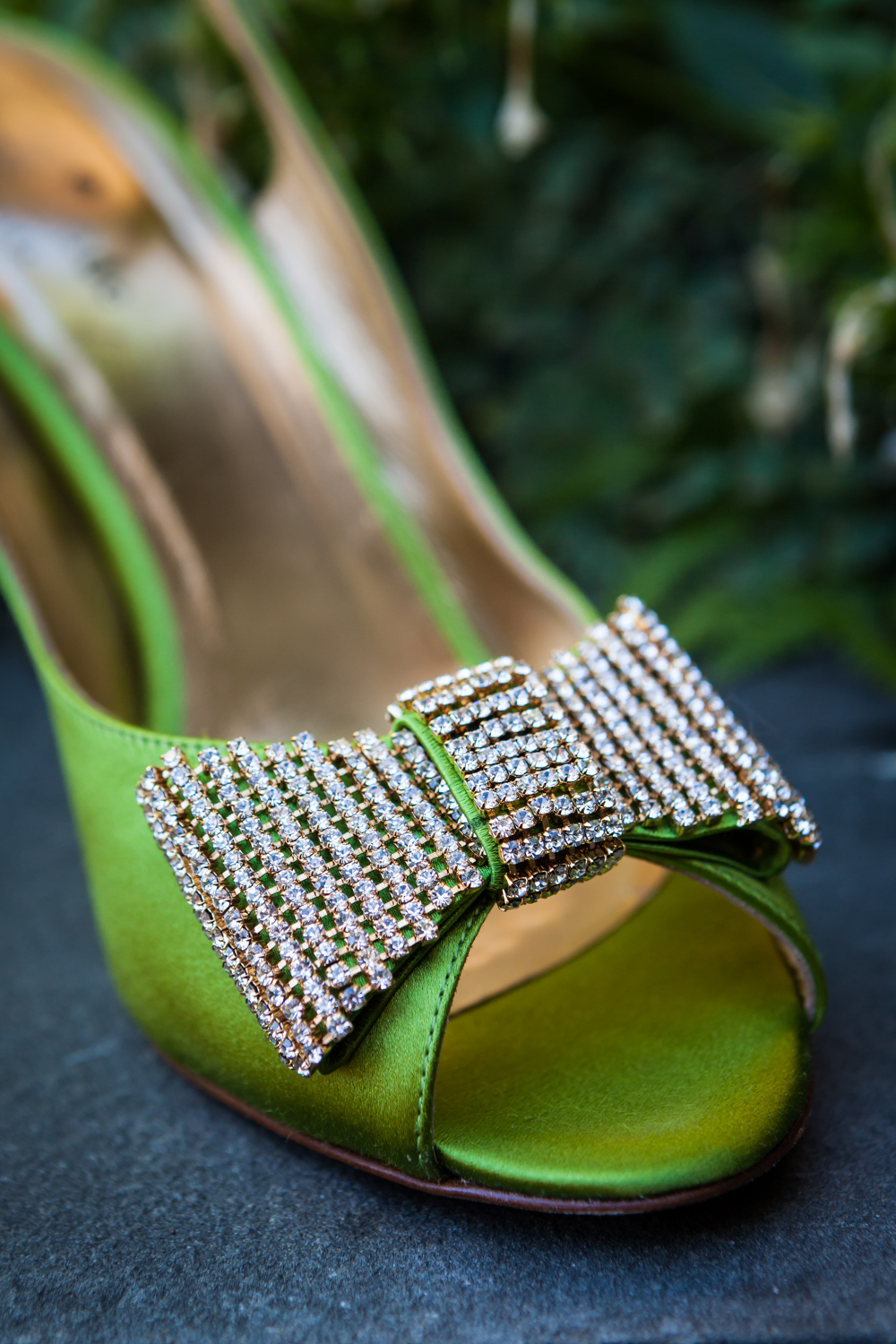 Close up on green satin high heel with diamond bow