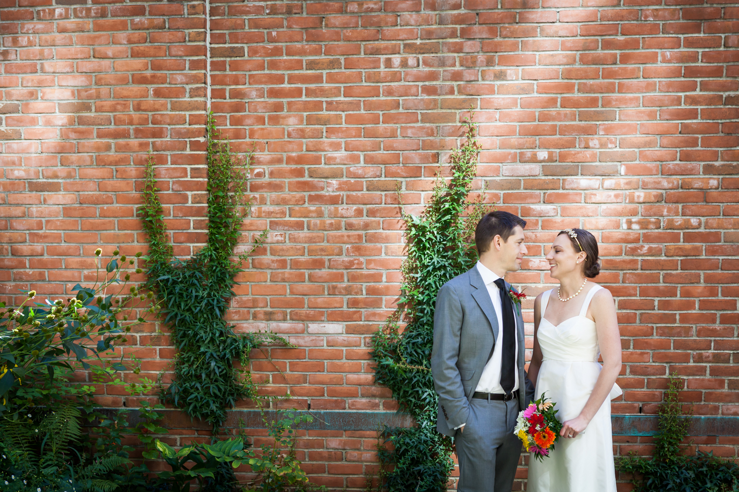 Merchant's House Museum wedding photos of bride and groom against brick wall