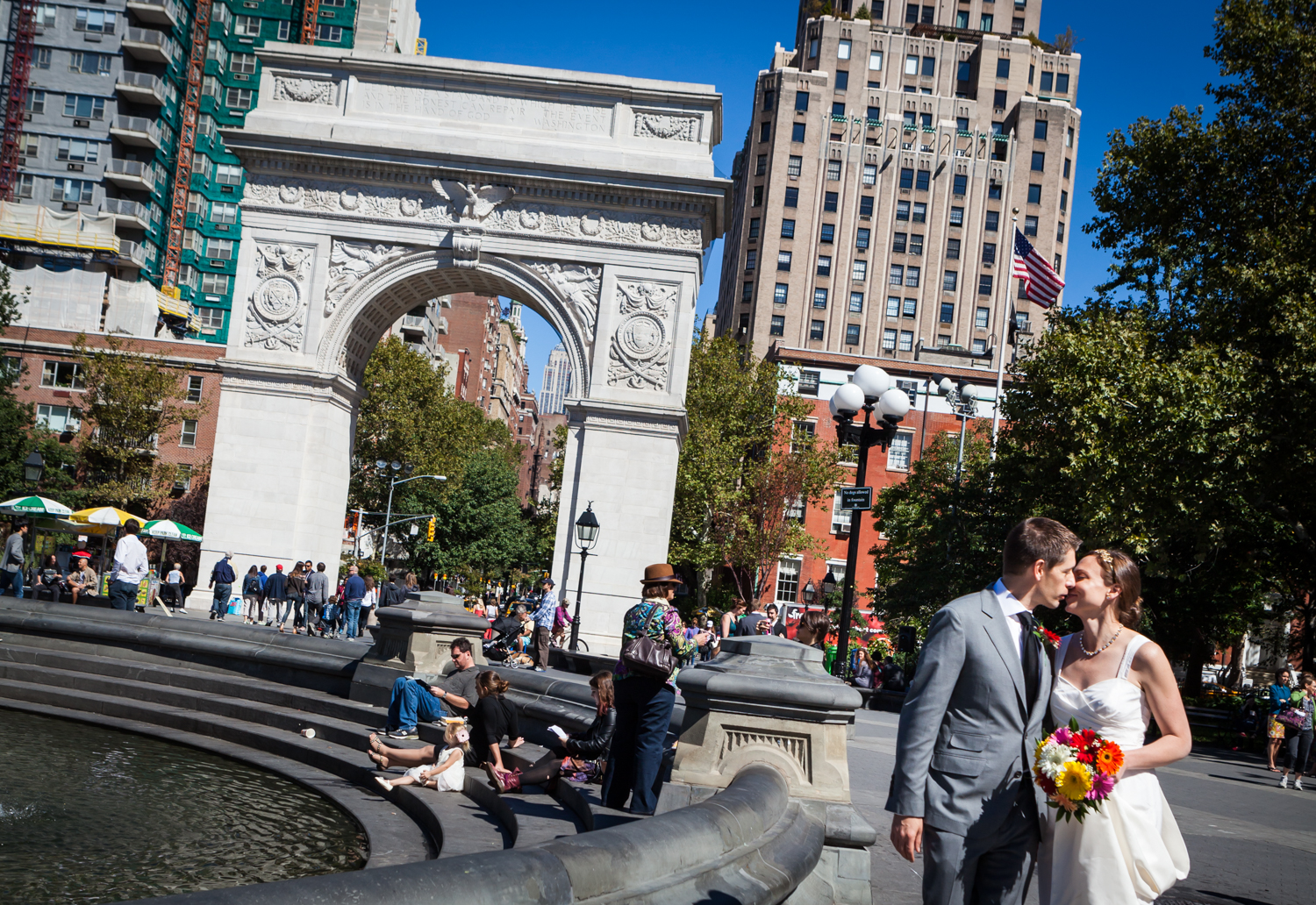 Bride and groom kissing with Washington Square Park arch in background